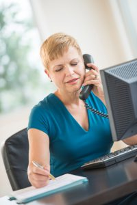 Businesswoman Using Landline Phone While Working At Desk