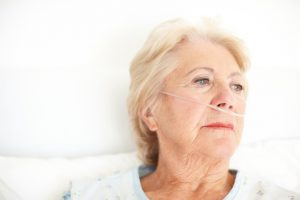 Ailing senior woman wearing a nasal cannula looking out of her hospital window thoughtfully