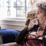 Portrait of an elderly woman sitting alone in a senior care facility