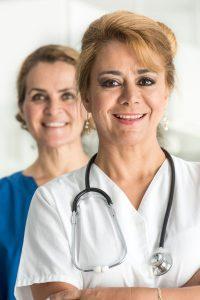 Mature Female doctors posing smiling looking at the camera