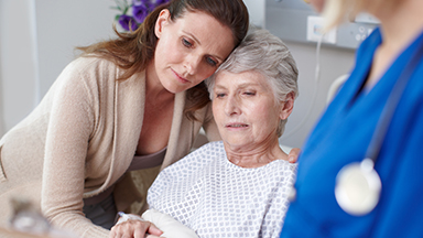 adult daughter embracing mom in hospital gown