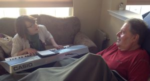 musician playing piano for hospice patient