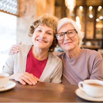 cheerful senior lady friends in coffee shop