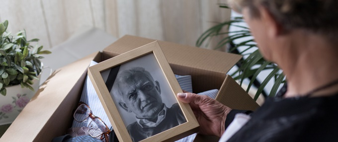 Grieving woman packing husband's belongings