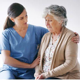 hospice nurse comforting elderly woman