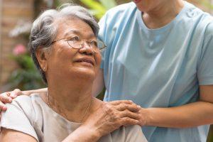 Caregiver holding hand of senior woman