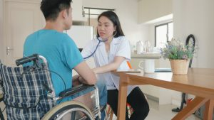 Home Care Worker Lwith Patient in Wheel Chair