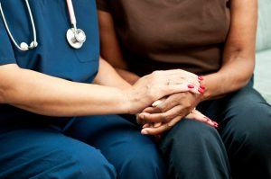 Healthcare worker holding the hands of a patient
