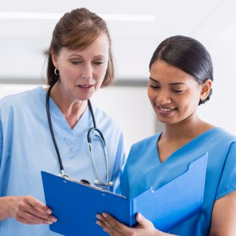 nurse and doctor discussing over clipboard