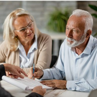 senior couple signing a contract while having a meeting with agent