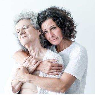 serious adult daughter embracing senior mother